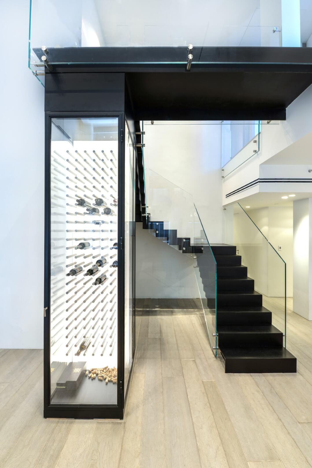 שני גרמי מדרגות ברזל עם מעקה זכוכית לצד מקרר יינות יוקרתי