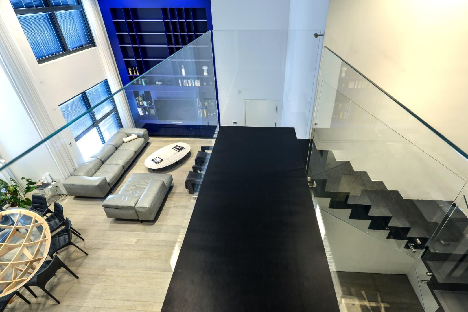 מבט מהקומה השניה על שני גרמי מדרגות ברזל עם מעקה הזכוכית והסלון המפואר בפנטהאוס