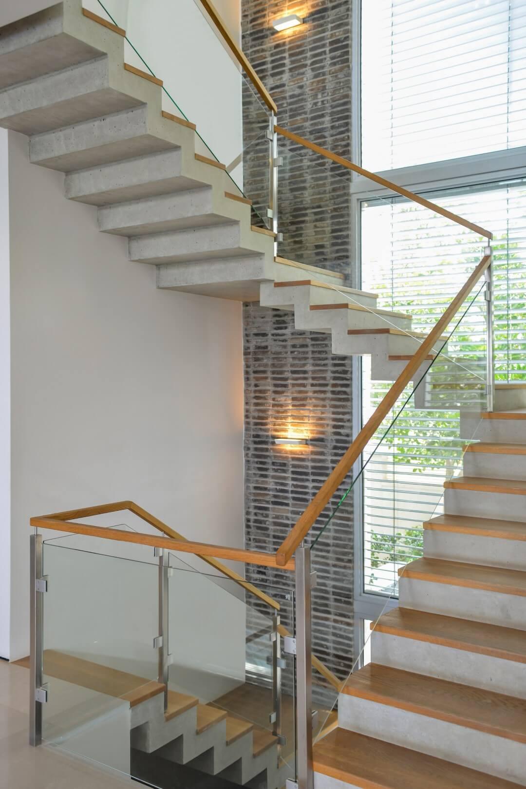 ארבעה גרמי מדרגות עץ אלון אמריקאי עם מעקה זכוכית ומאחז יד מעץ בצמוד לחלון ויטרינה עצום