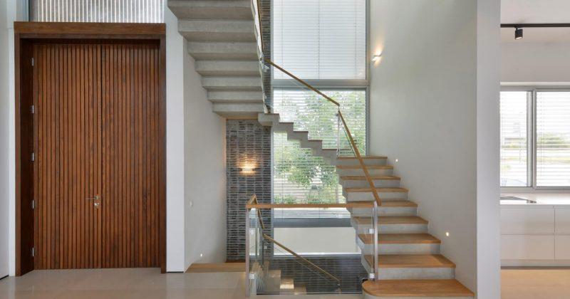 שלושה גרמי מדרגות עץ אלון אמריקאי בשילוב של מעקה זכוכית ומאחז יד מעץ בסמוך לכניסה לוילה