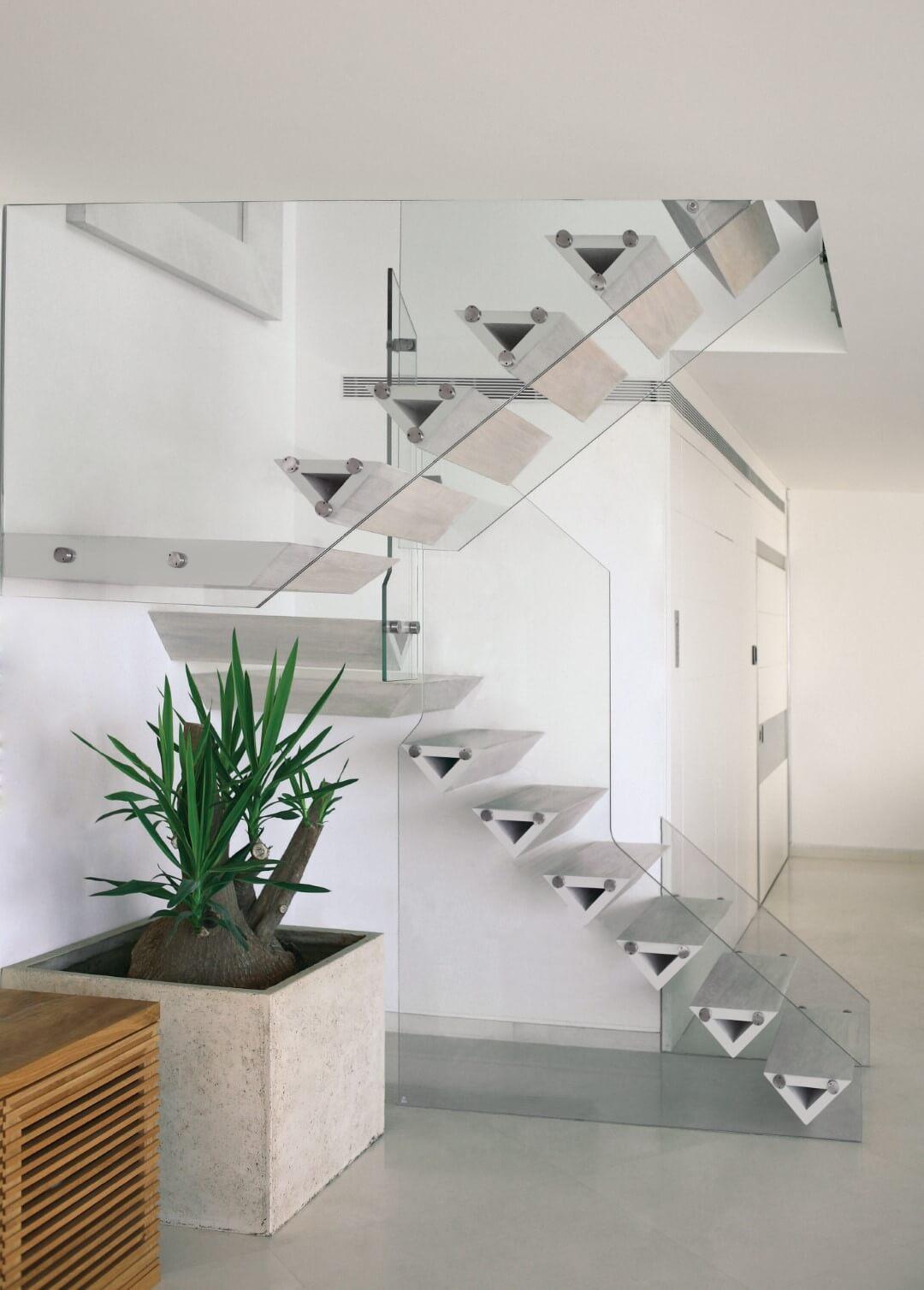 מדרגות עץ האלון כאילו תלויות באוויר בין שני מעקי זכוכית