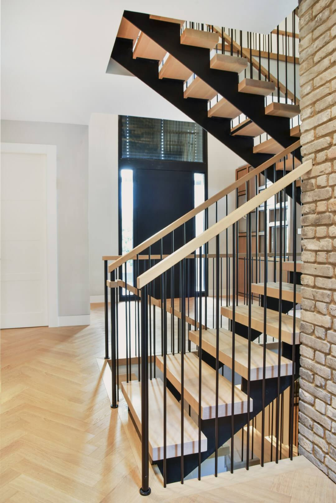 2 גרמי מדרגות ברזל עם מעקה ברזל, מאחז יד מעץ ומדרכי עץ אלון אמריקאי שמתכתבים עם הפרקט