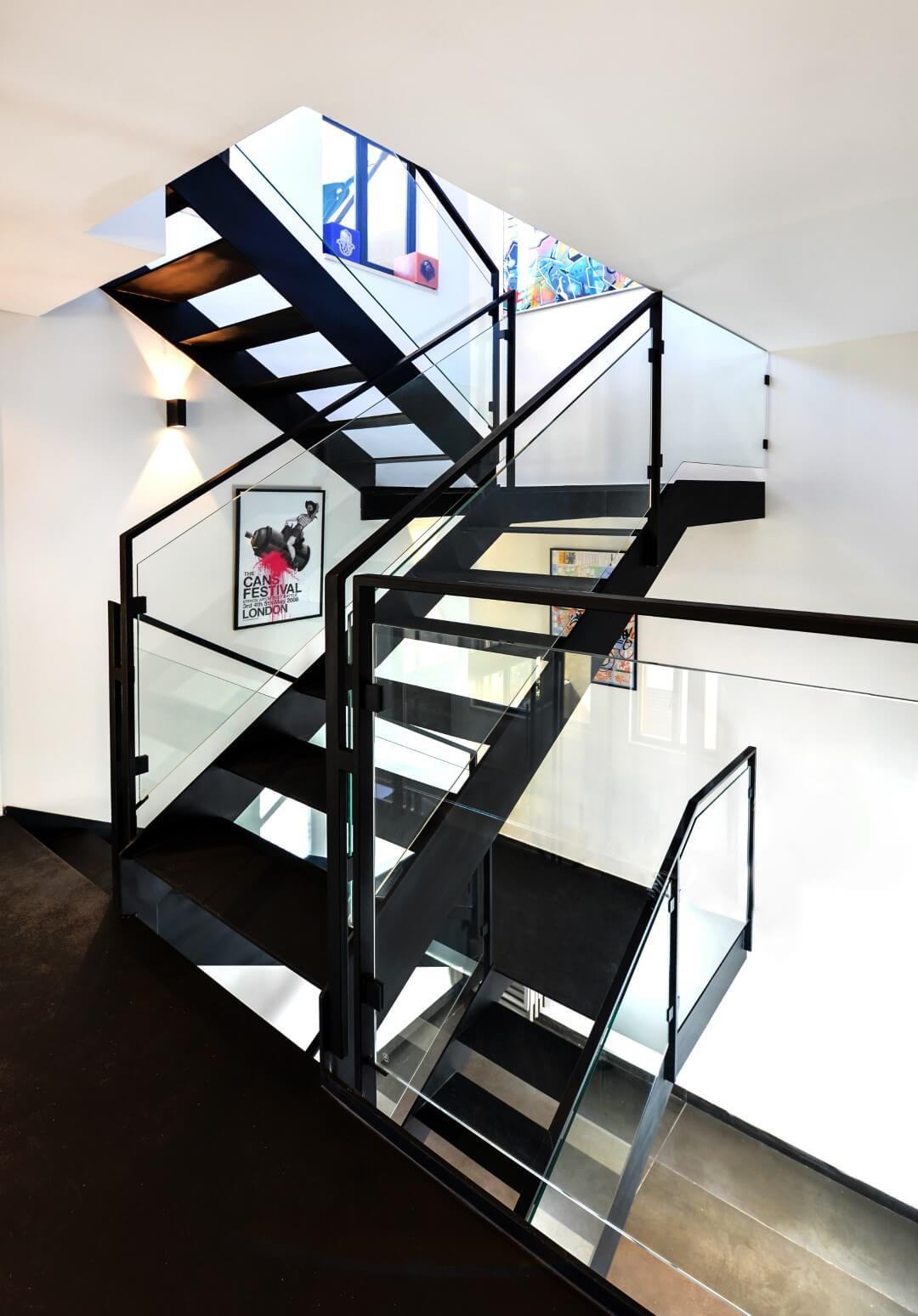 שלושה גמרי מדרגות מברזל שחור מעוצב עם מעקה זכוכית וברזל