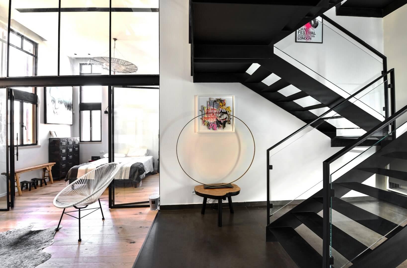 שני גרמי מדרגות ברזל שחור עם מעקה ברזל בשילוב זכוכית מחברים בין קומות הוילה