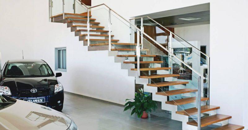 שני גרמי מדרגות נירוסטה בלבן עם מדרכי עץ אירוקו בגווני נחושת, מדבר וחימר קדרים בליווי של מעקה זכוכית ומאחז יד מנירוסטה