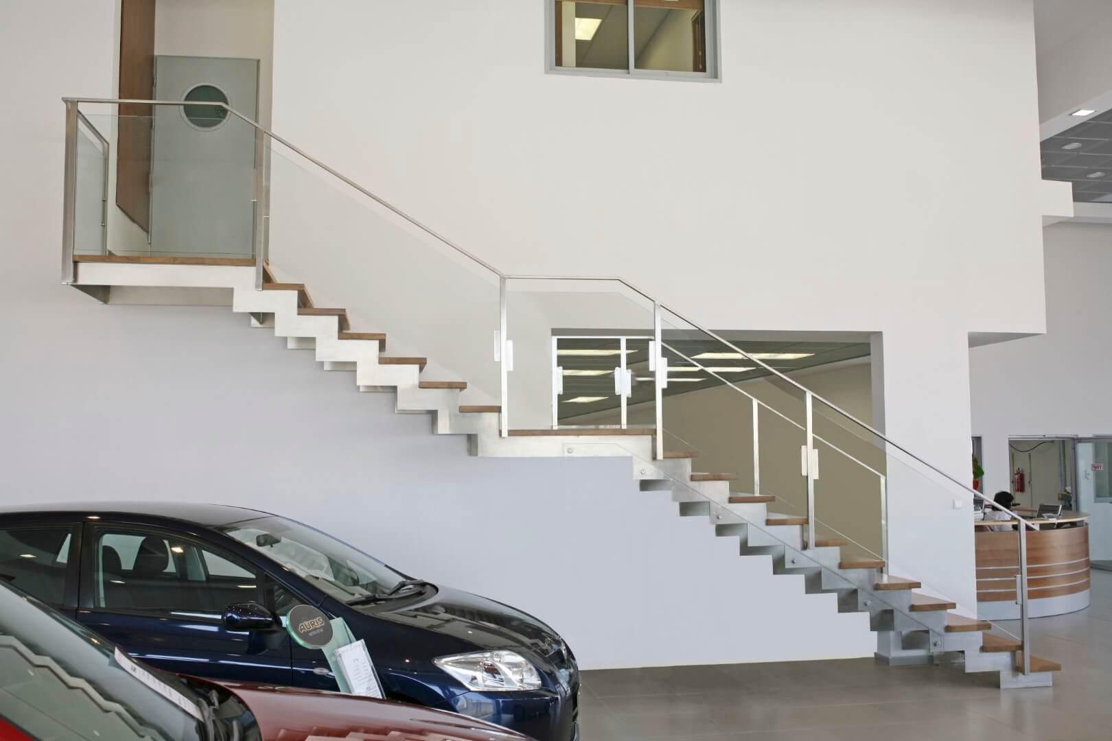 שני גרמי מדרגות נירוסטה עם מדרכי עץ עולים אל משרדי אולם התצוגה לאורכו של קיר לבן ונקי