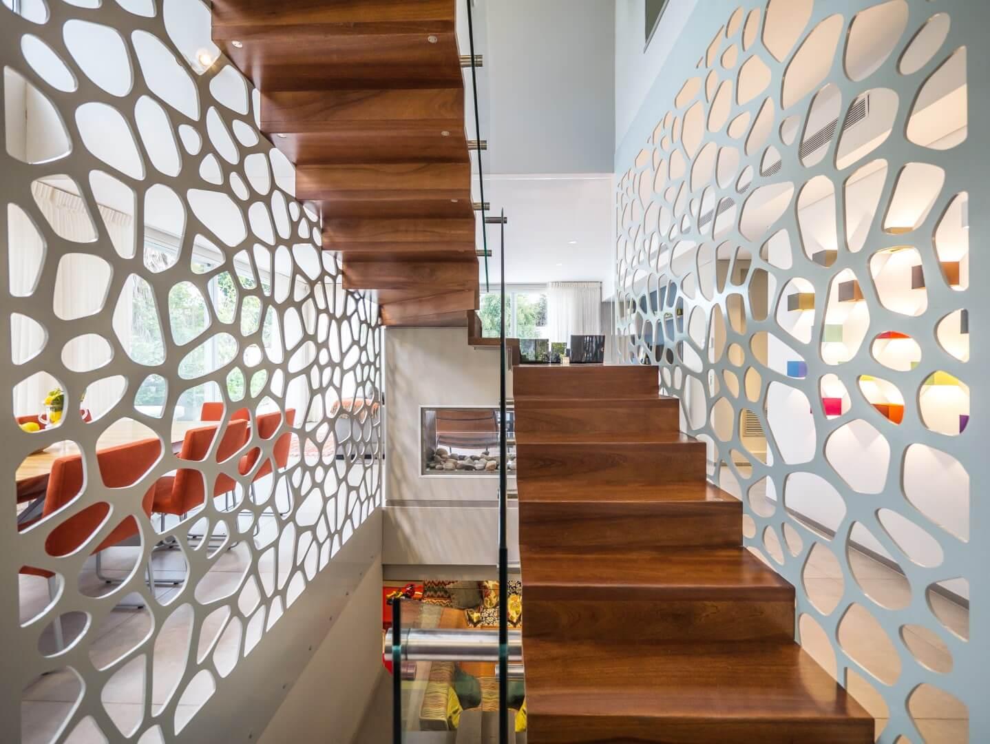 שני שלחי מדרגות מרחפות מעץ ספלי עם מעקה זכוכית מוקפת מחיצה לבנה מעוצבת בדירה ברעננה