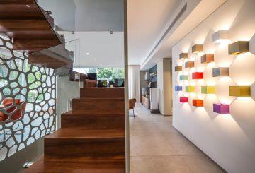 שני גרמי מדרגות עץ מרחפות מעץ ספלי עם מעקה זכוכית על רקע קיר לבן עם תאורה צבעונית