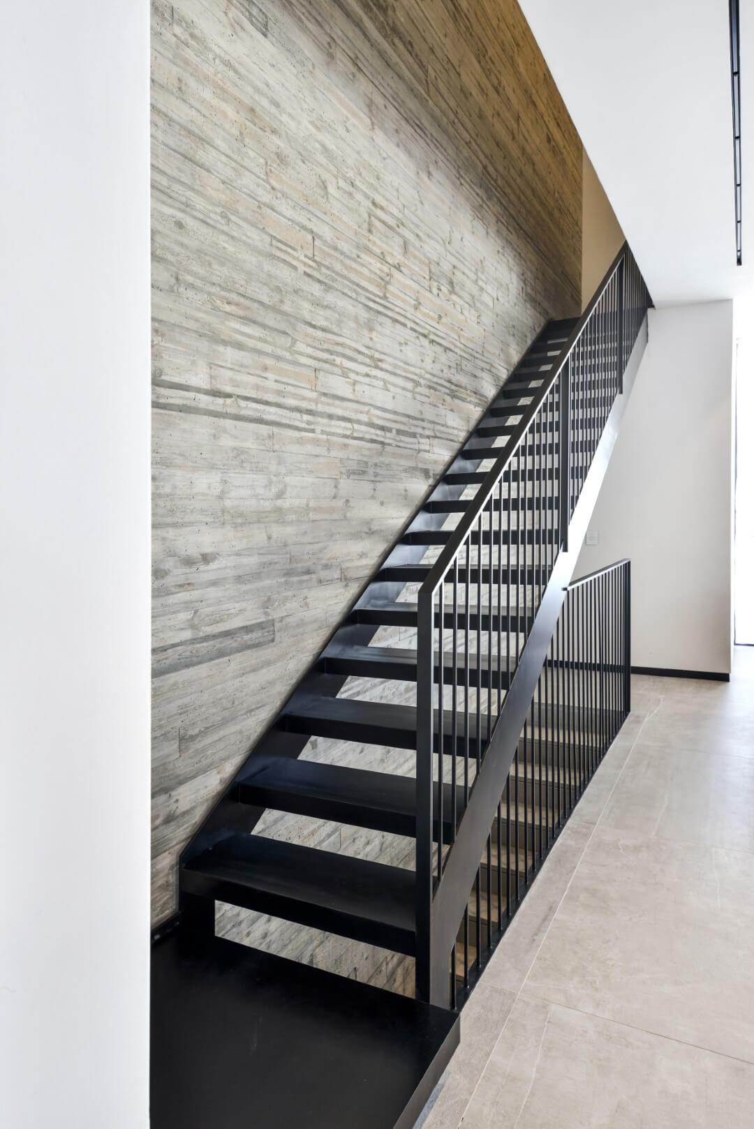 גרם מדרגות ברזל שחור מחבר בין שתי הקומות בליווי של מעקה ברזל שחור
