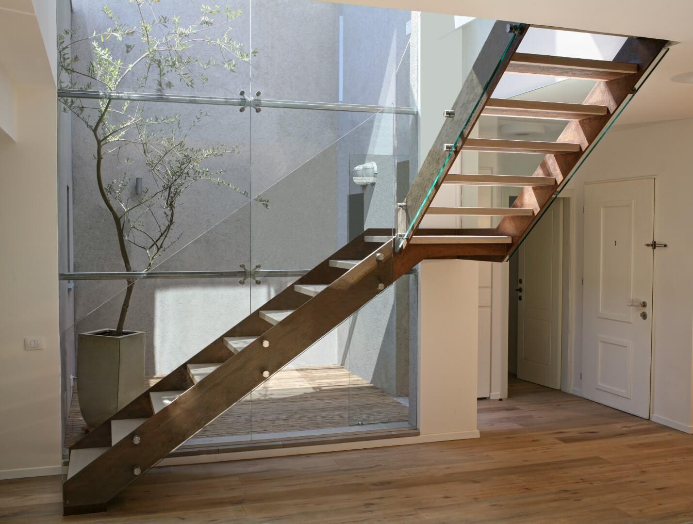 מבט על שני גרמי מדרגות מרחפות מברזל, קורטן ועץ אלון אמריקאי מולבן עם מעקה זכוכית המחברות בין שתי קומות הבית
