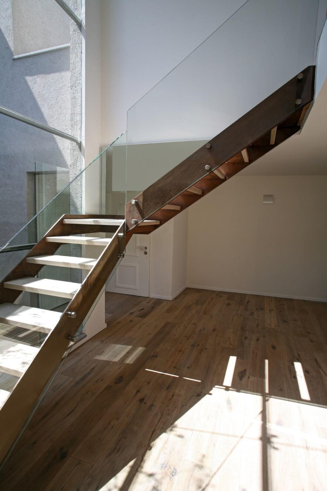 עם הפנים לגרם מדרגות צפות מברזל, קורטן ועץ עם מעקה זכוכית