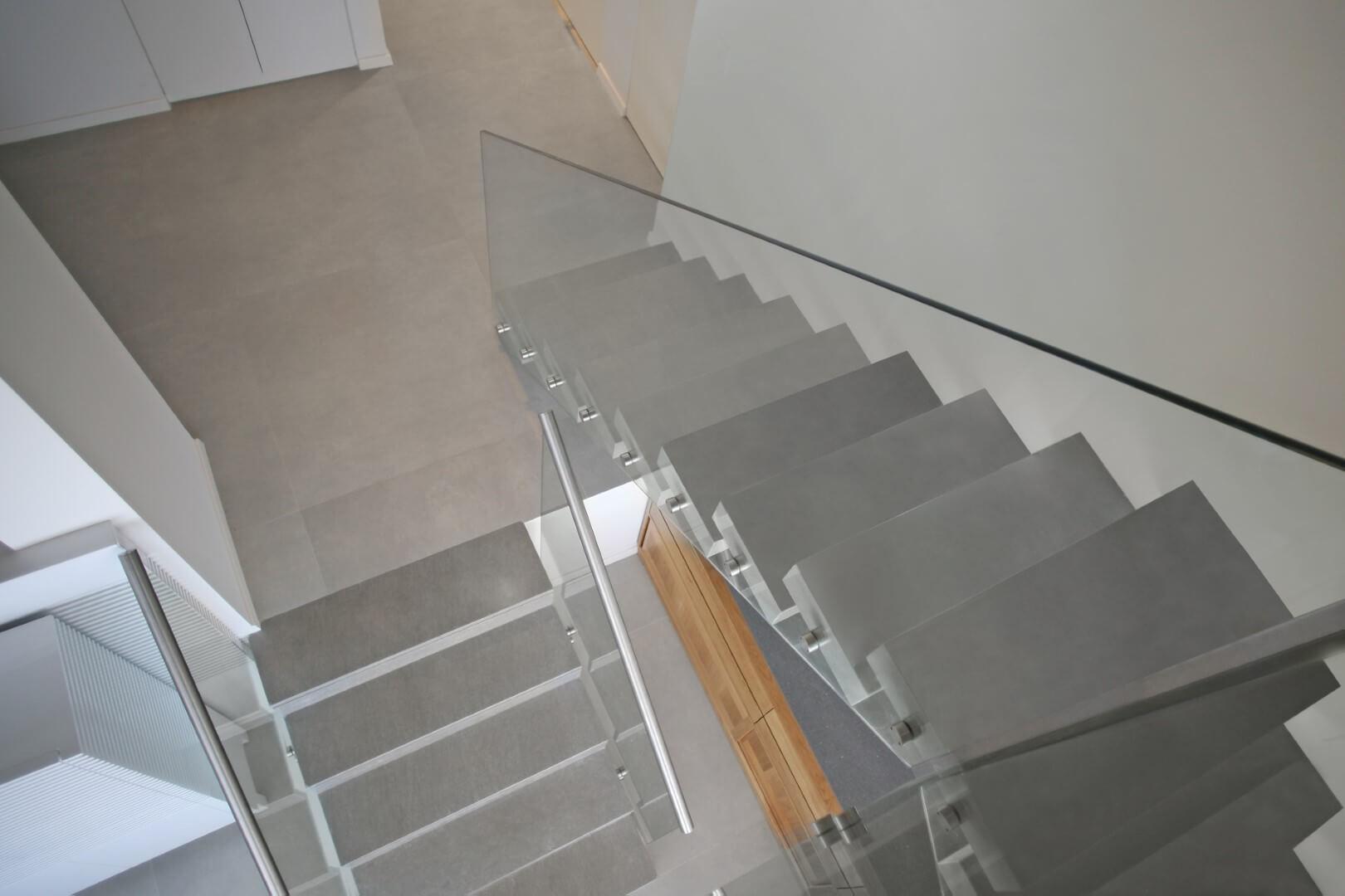 מבט על על שני גרמי מדרגות מרחפות משיש עם מעקה זכוכית שקוף