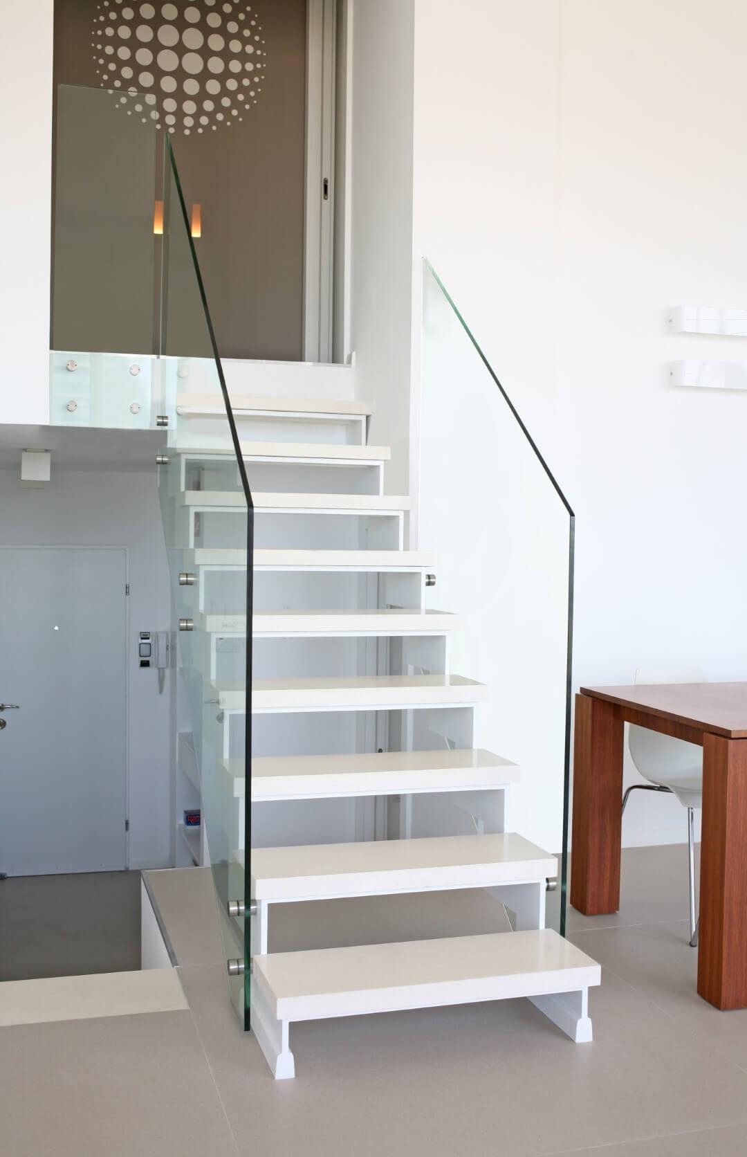 מדרגות צפות משיש לבן עם מעקה זכוכית שקוף מחברות את שתי קומות בוילה