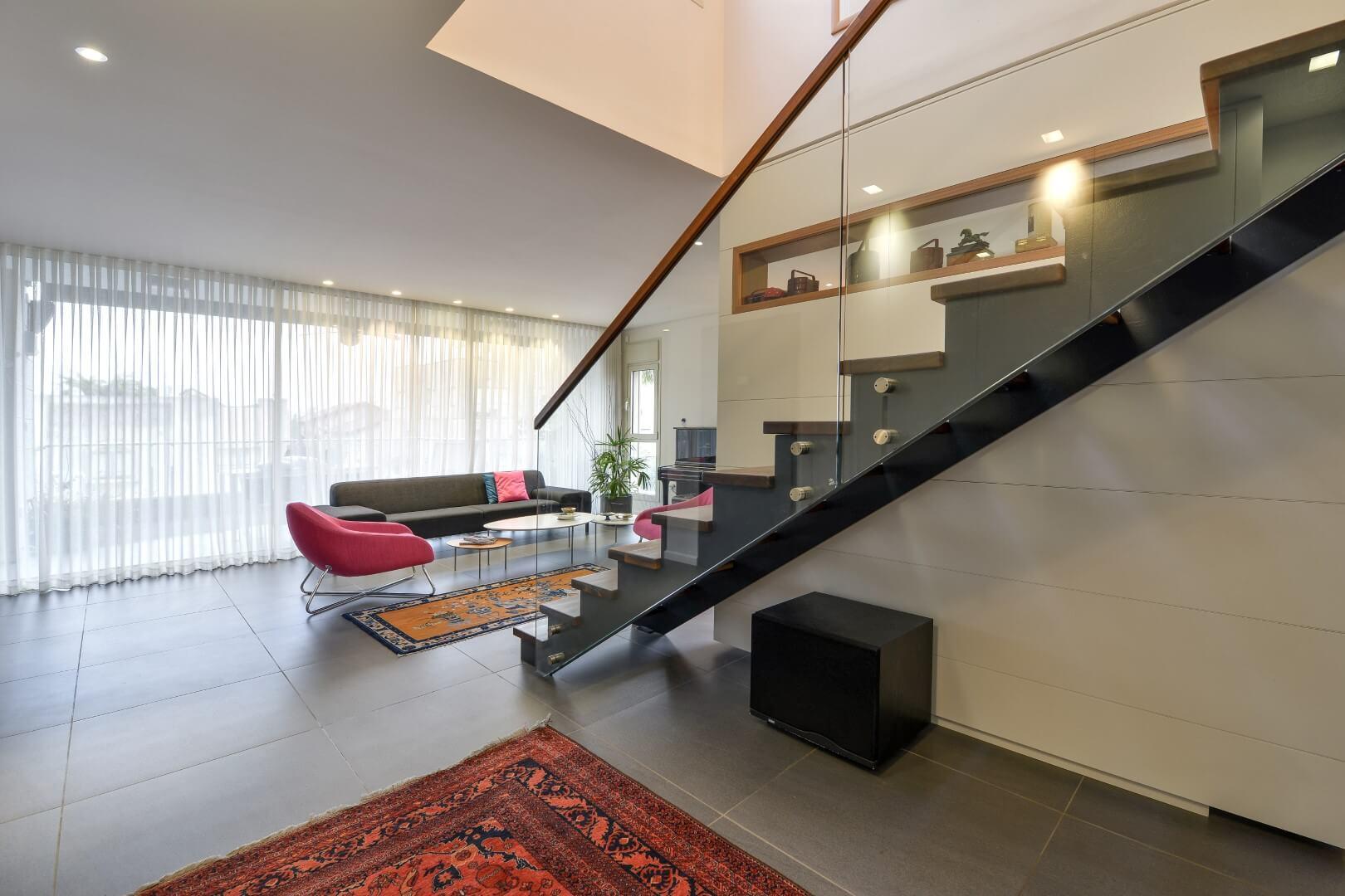 מדרגות ברזל שחור עם מדרכי עץ אגוז אמריקאי, מעקה זכוכית ומאחז יד מעץ בקצה