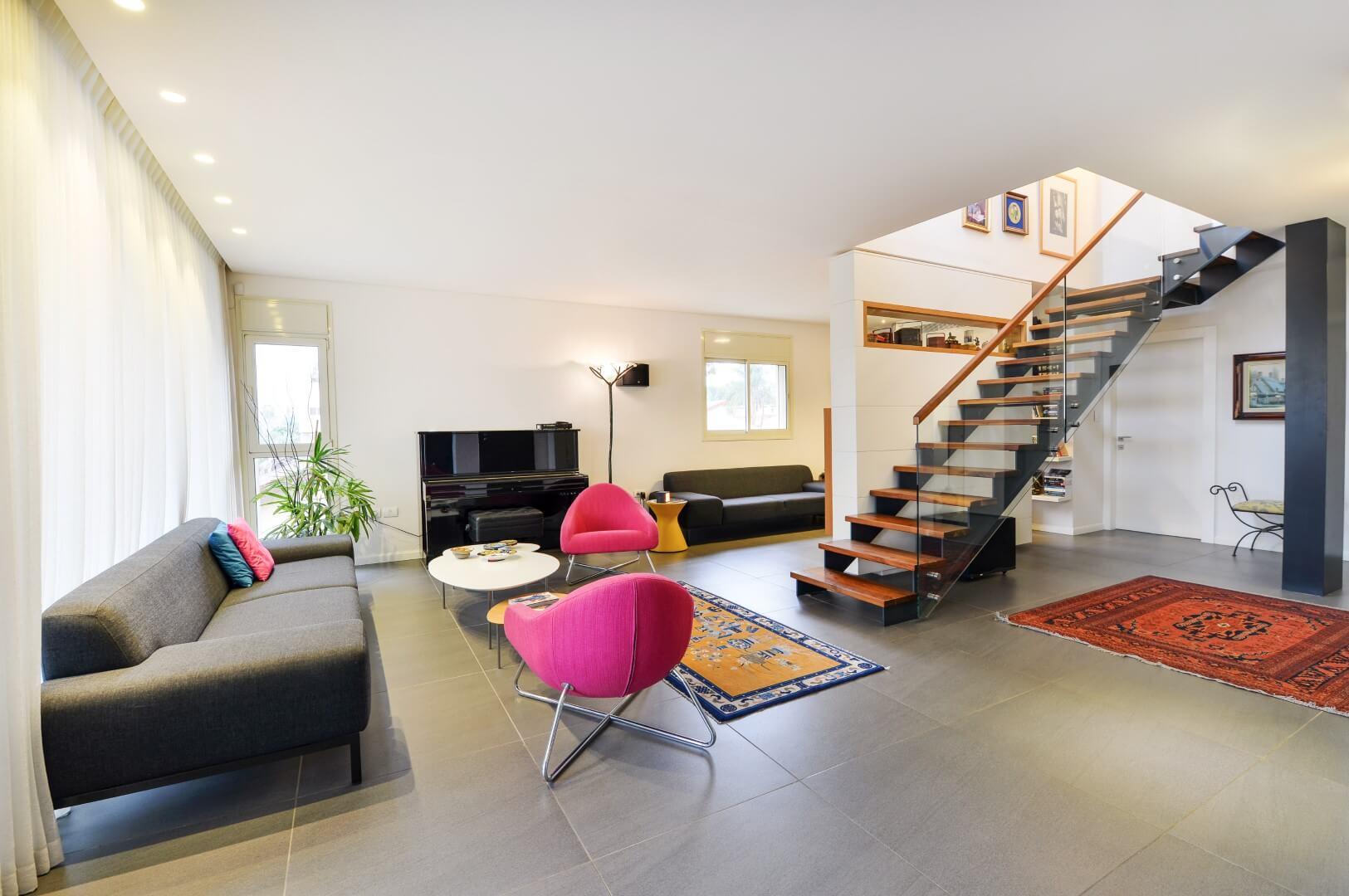 מדרגות ברזל שחור עם מעקה זכוכית, מאחז יד מעץ ומדרכי עץ אלון שלוקחים את הדיירים מהסלון האפור אל הקומה השניה של הוילה
