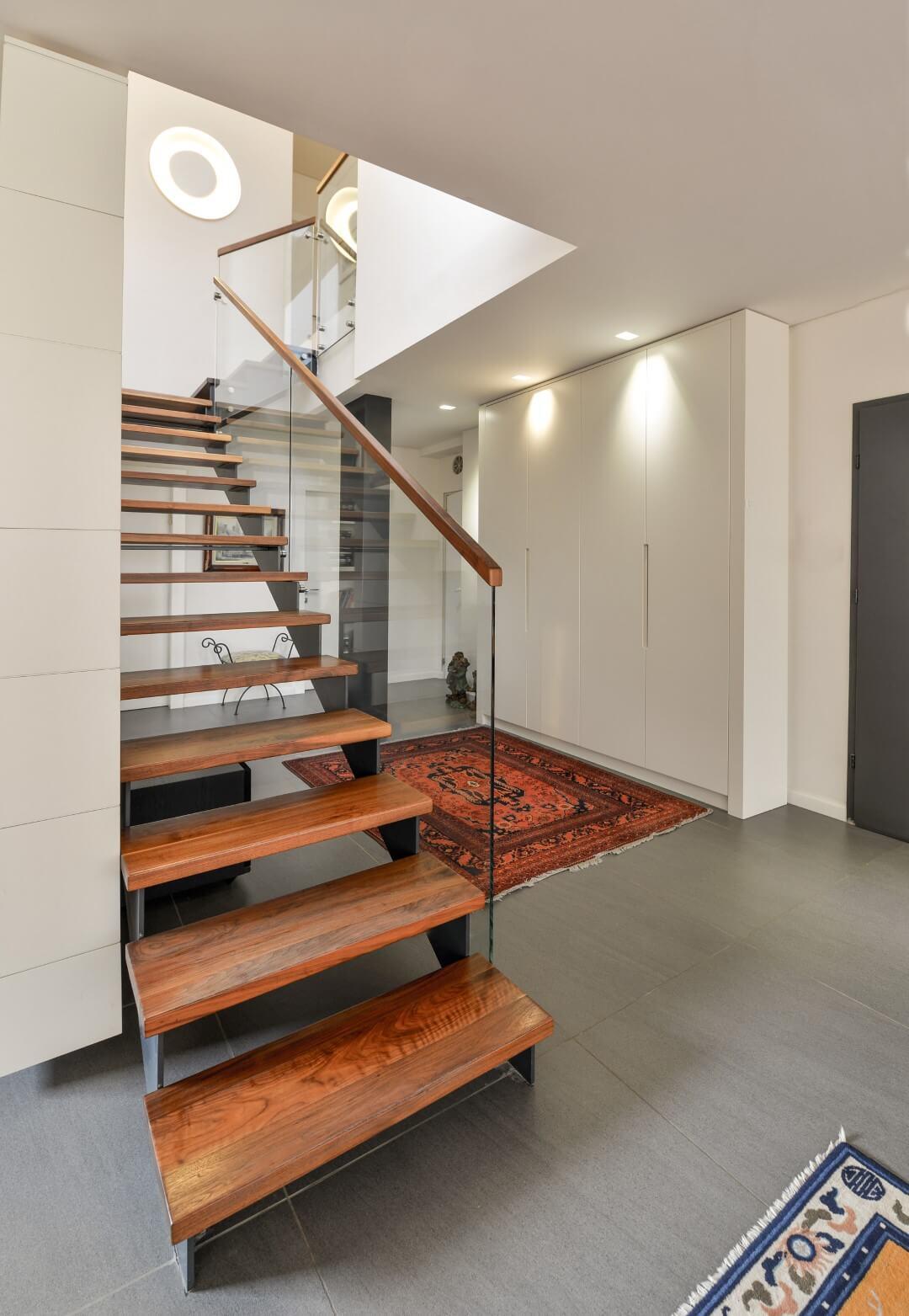 מדרגות ברזל שחור עם מעקה זכוכית ומאחז יד מעץ שמחזיקים מדרכי עץ אגוז אמריקאי בגוונים של חום חלוד, ושיזוף הוואי