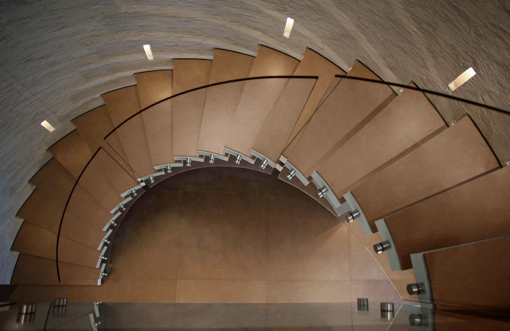 מבט מלמעלה על מדרגות לולייניות ספיראלה מקוריאן עם מעקה ספירלי מזכוכית