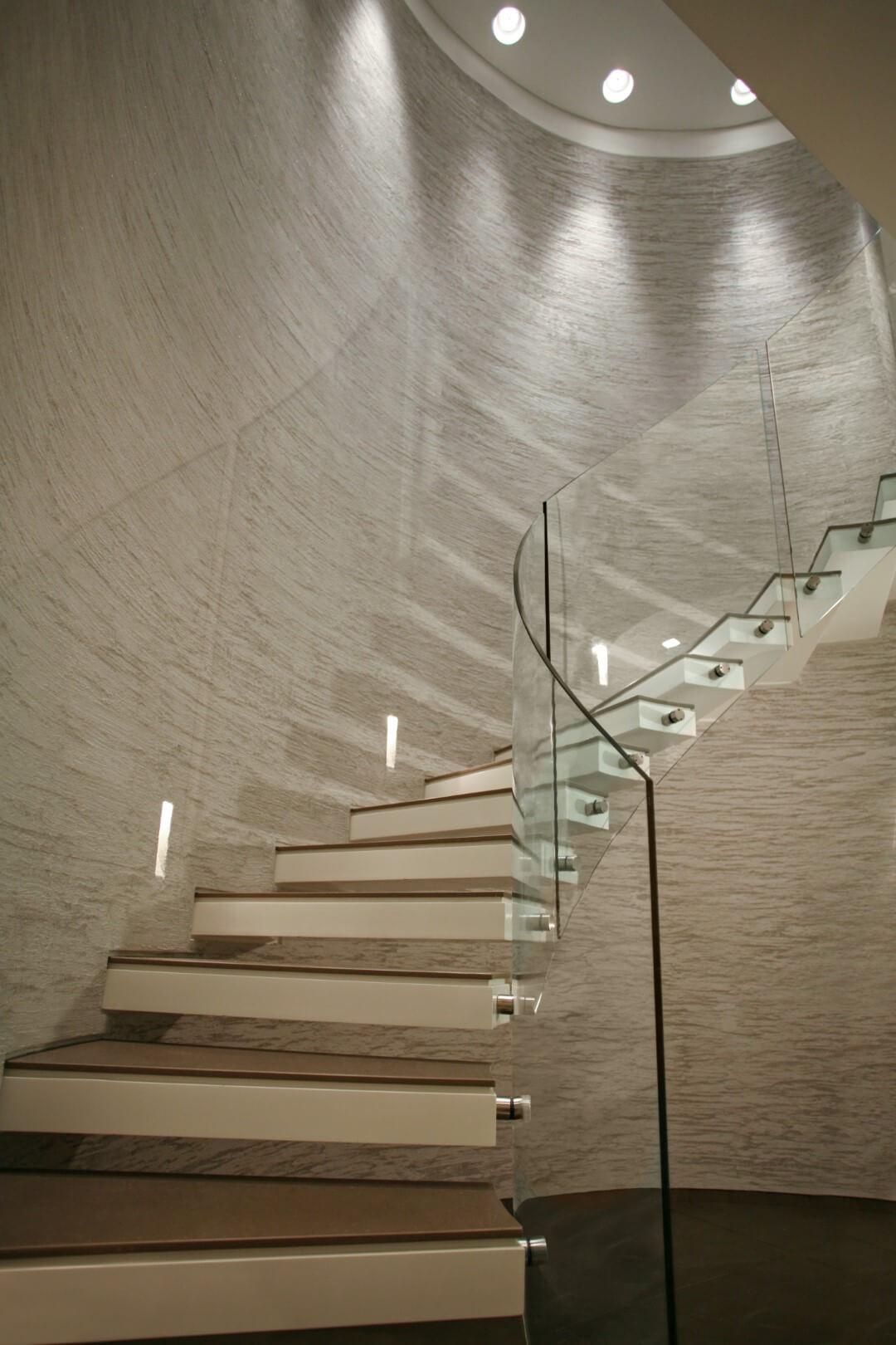 מדרגות ספירליות מקוריאן עם מעקה ספירלי מזכוכית עולות לקומה השניה לאורך הקיר