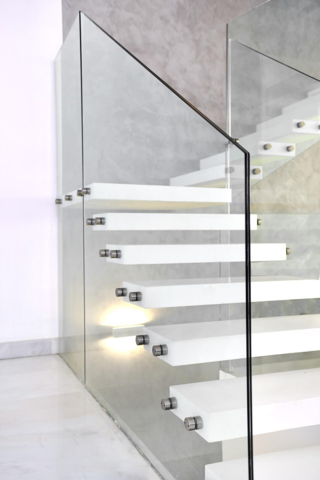 תקריב של מעקה הזכוכית ומדרכי הקוריאן הלבן של המדרגות