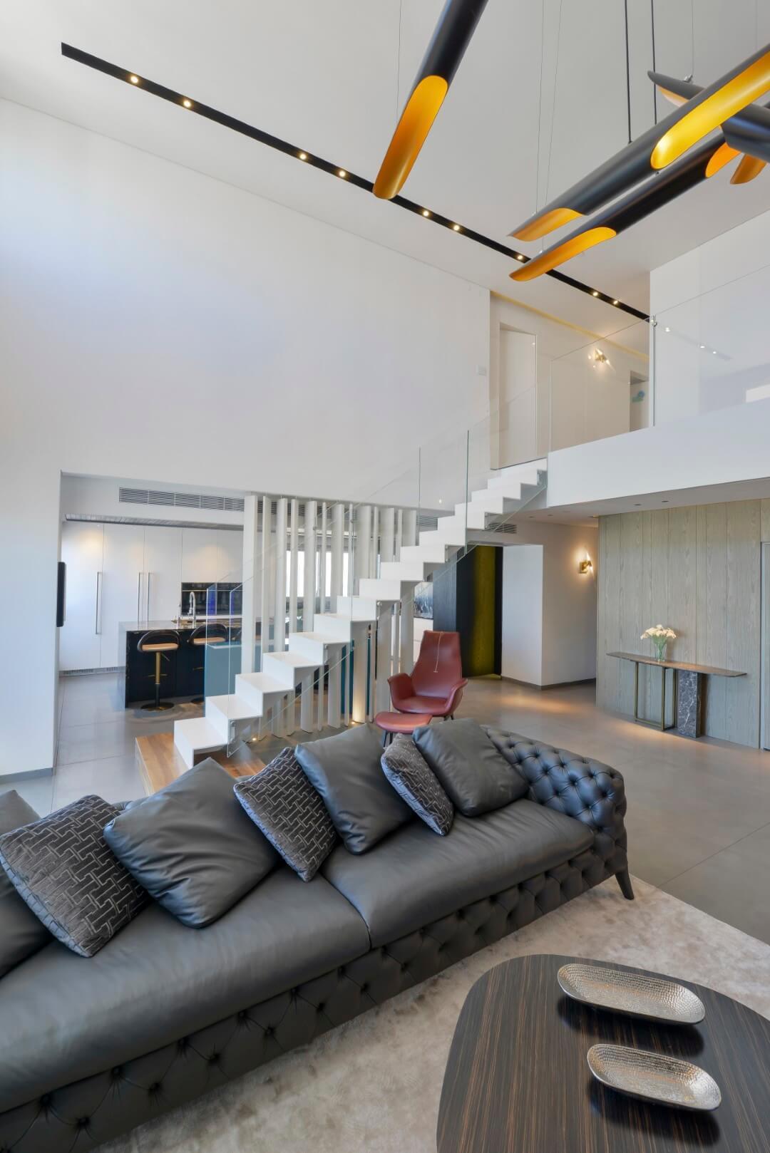 מבט מהסלון אל מדרגות הברזל המרחפות בצבע לבן שעולות אל הקומה השניה