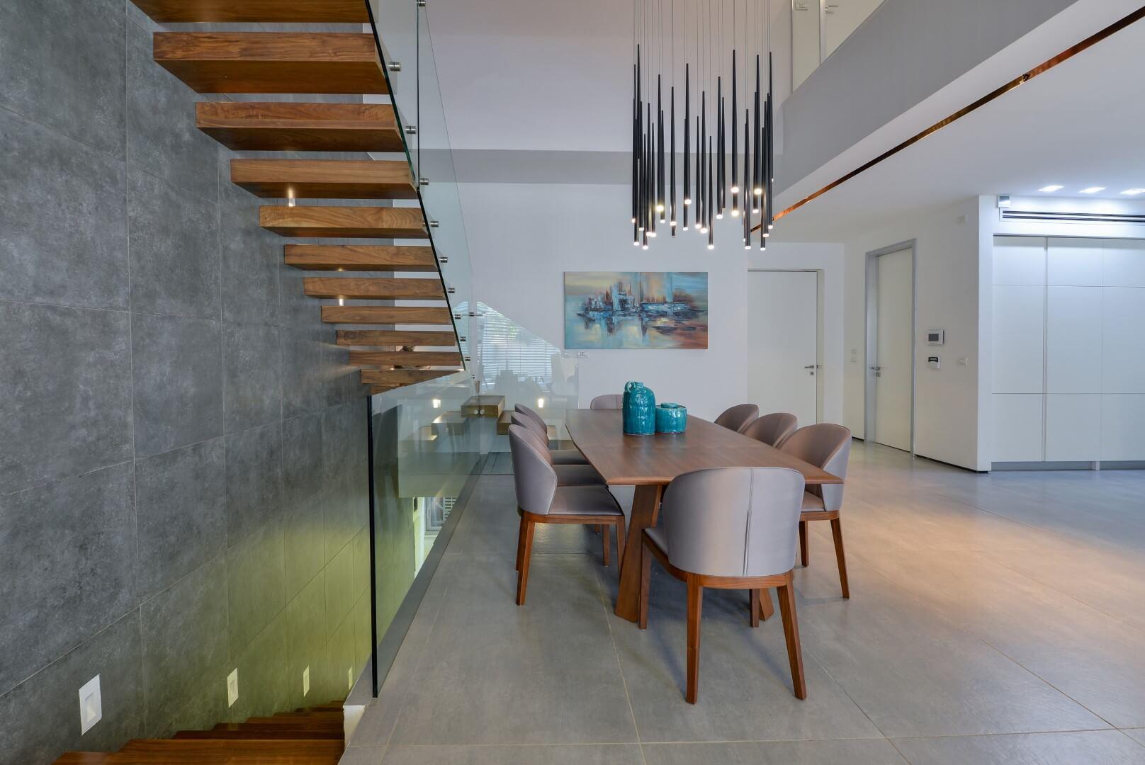 שני גרמי מדרגות מרחפות מעץ אגוז אמריקאי ומעקה זכוכית שמחברים 3 קומות בוילה