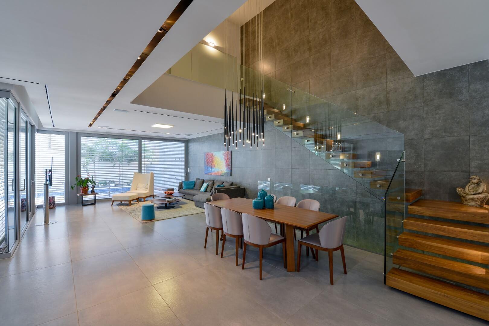 שני גרמי מדרגות מרחפות מעץ אגוז אמריקאי ומעקה זכוכית שמחברים 2 קומות בוילה