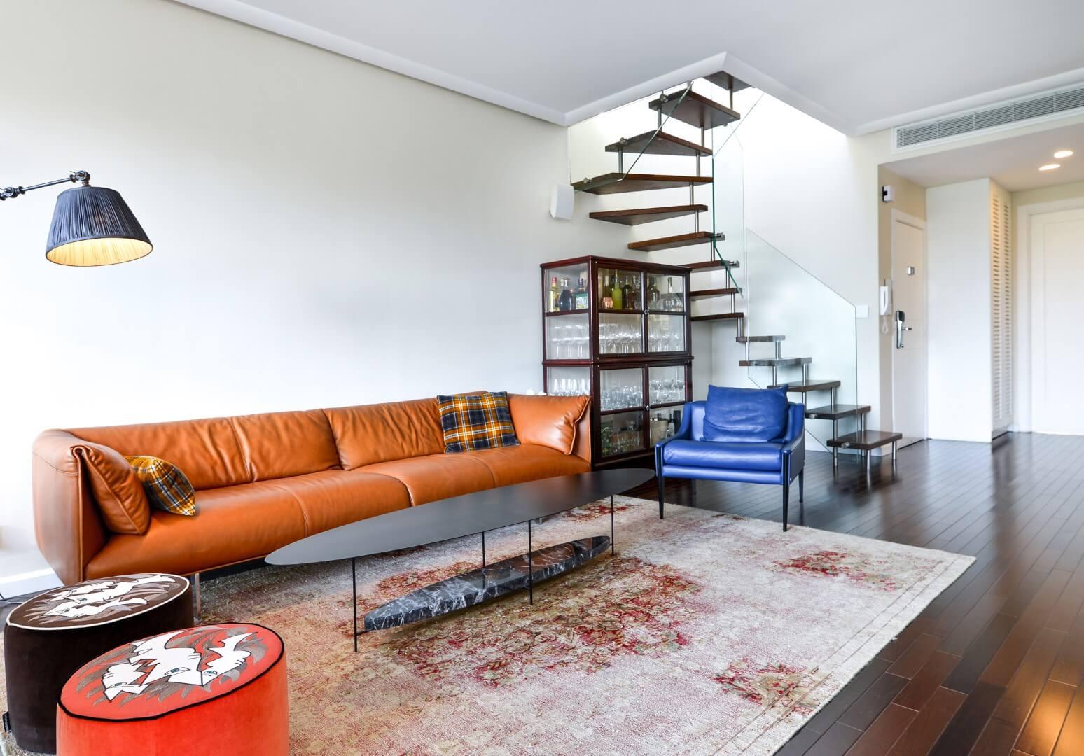 מדרגות צפות עם מדרכי עץ אלון בגוונים של כתום גס ומדבר ומעקה זכוכית בסלון