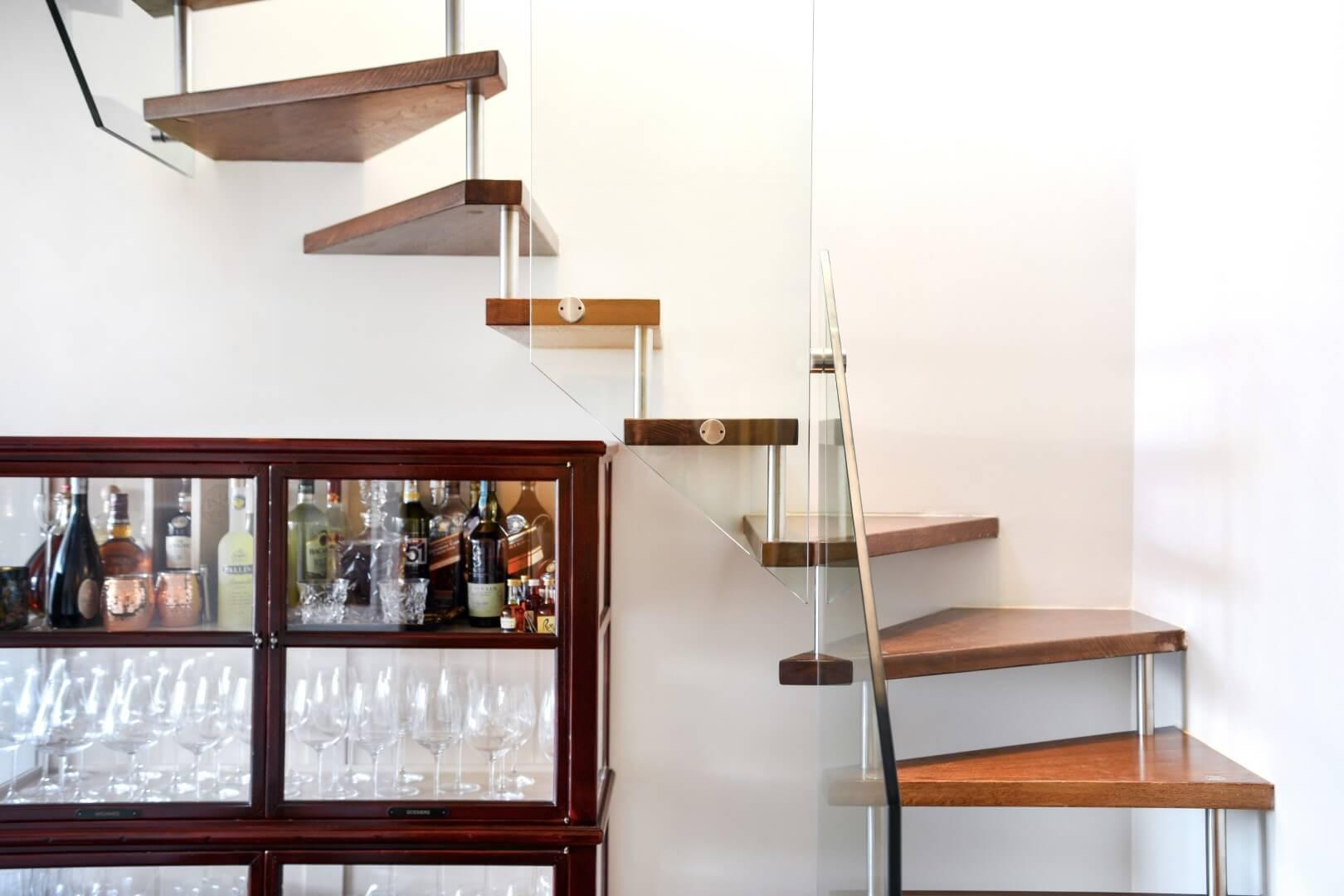 מדרגות עץ מרחפות עם ספייסרים מנירוסטה ועץ אלון מגוון לפי פרקט עם מעקה זכוכית