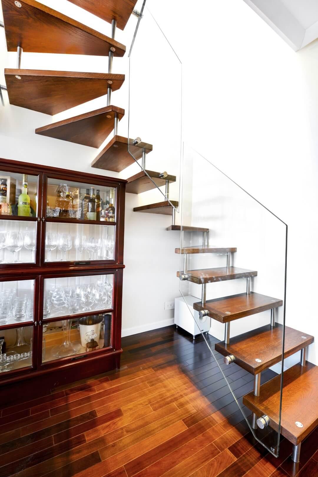 מדרגות צפות עם מדרכי עץ אלון בגווני זהב עמוק וכתם גס בלווי מעקה זכוכית על רקע רצפת פרקע בגוונים תואמים