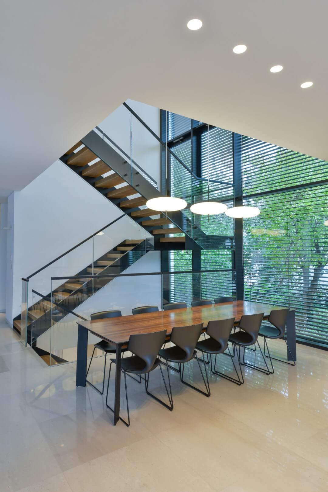 מדרגות קונסטרוקציות ברזל כפולה דקה וביניהם מדרגות עץ ומעקה זכוכית 8+8 קליר בצד הברזל פרזול שחור