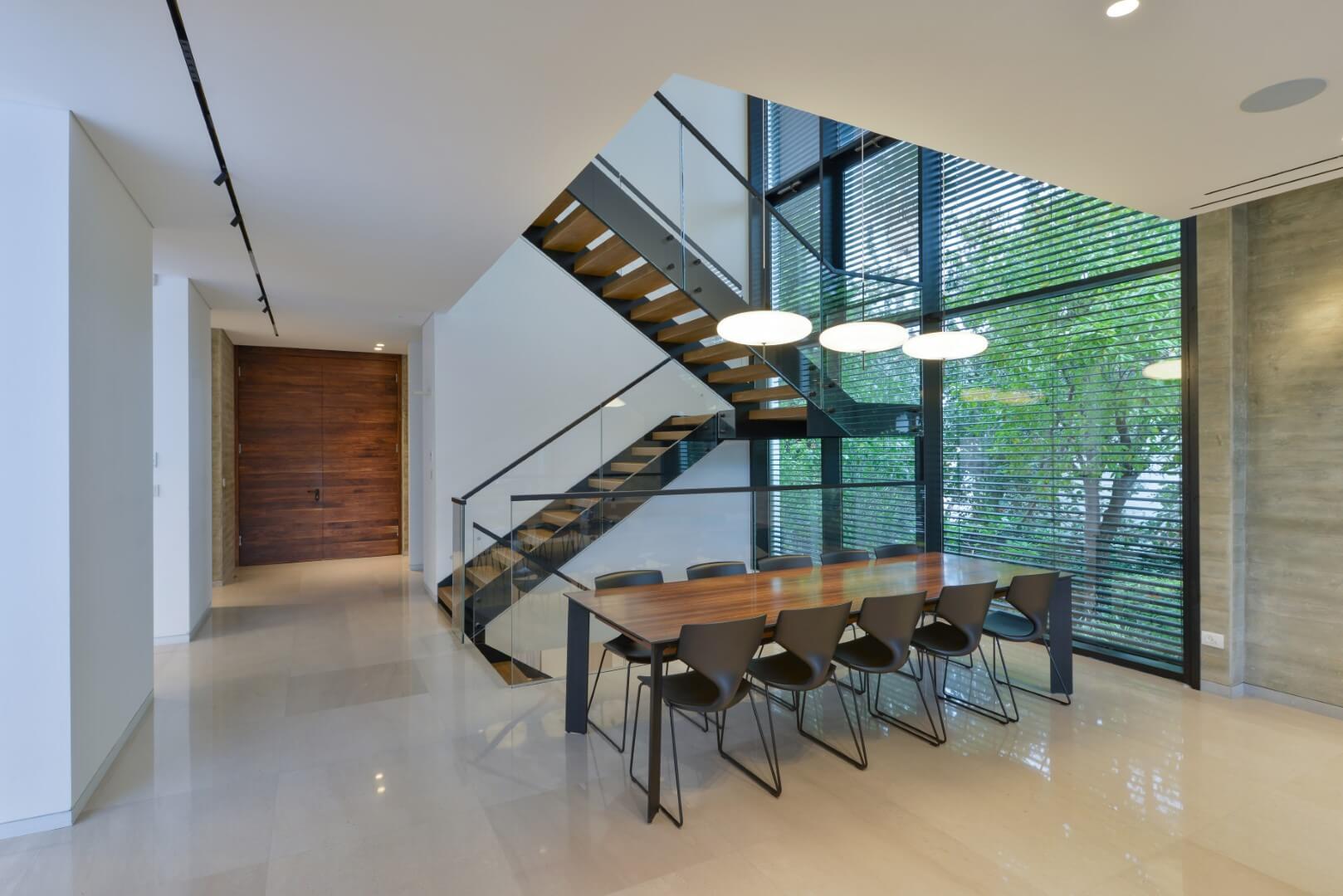 שני גרמי מדרגות עץ בנוים בתוך קונסטרוקצית ברזל שחור עם מעקה זכוכית ומאחז יד ממתכת