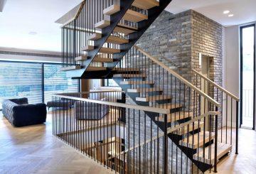 3 גרמי מדרגות ברזל עם מעקה ברזל, מאחז יד מעץ ומדרכי עץ אלון אמריקאי על רקע קיר בריקים