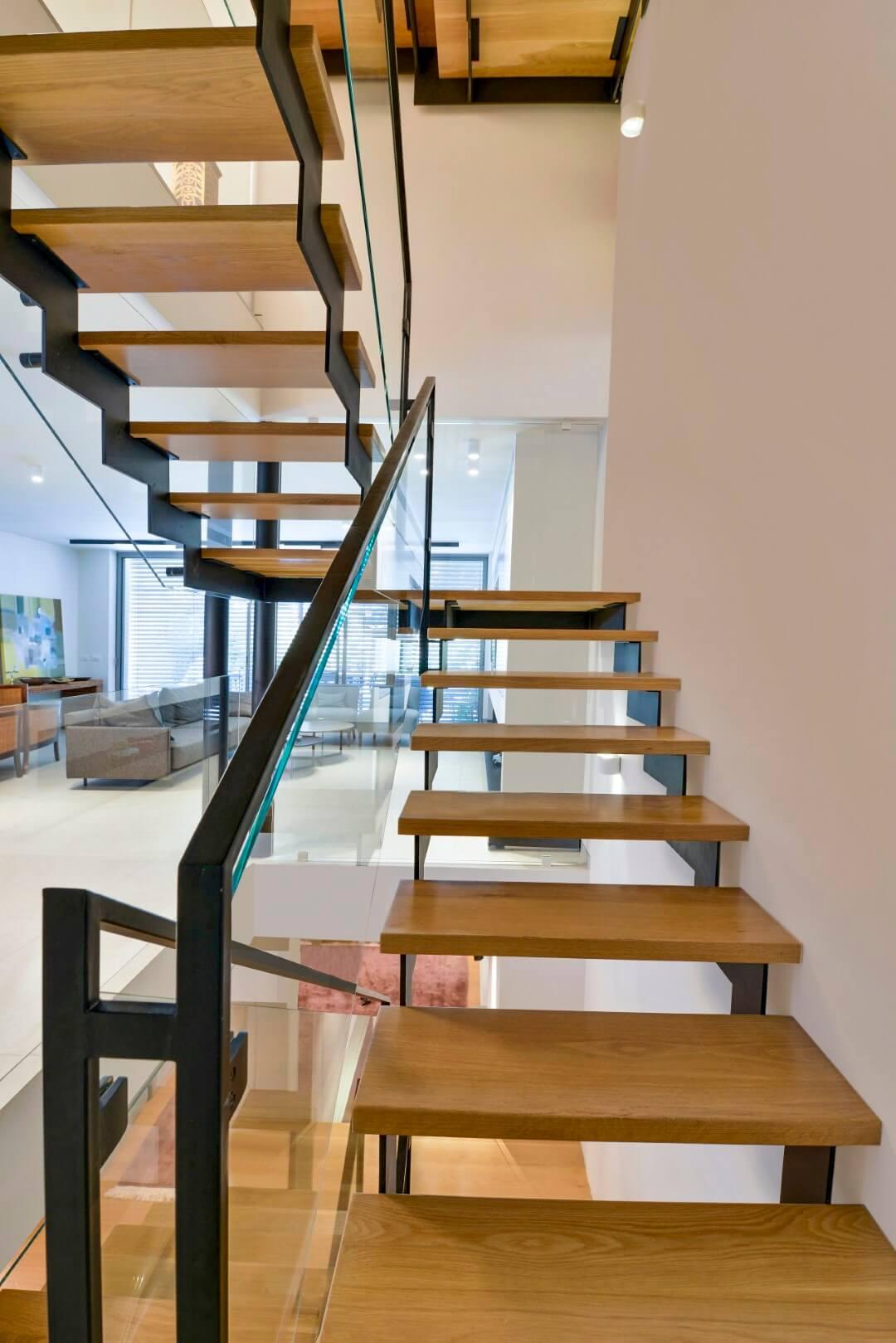 מבט מגרם מדרגות הברזל דרך מדרכי עץ האלון על סלון הבית