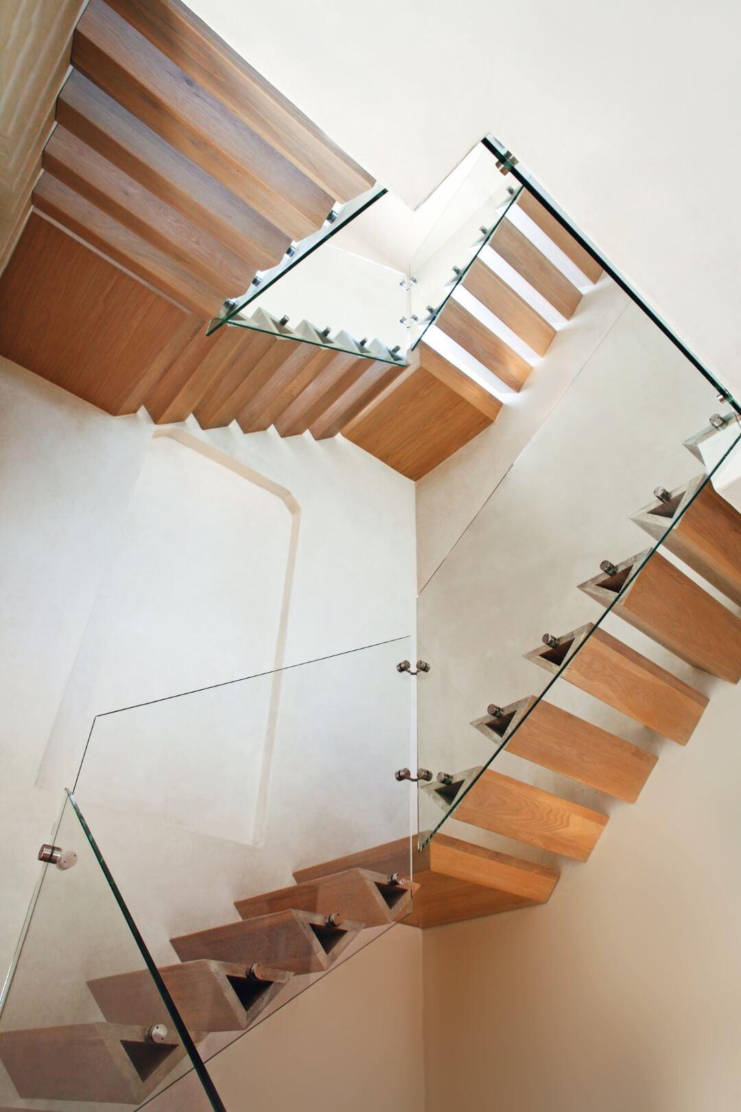 מבט דרך חמישה גרמי מדרגות מרחפות עם מדרכי עץ משולשים שעולים למעלה ומחברים את מפלסי הבית
