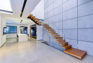 שני גרמי מדרגות צפות ארוכים מעץ אלון בגווני נחושת אספרסו עם מעקה זכוכית קליר