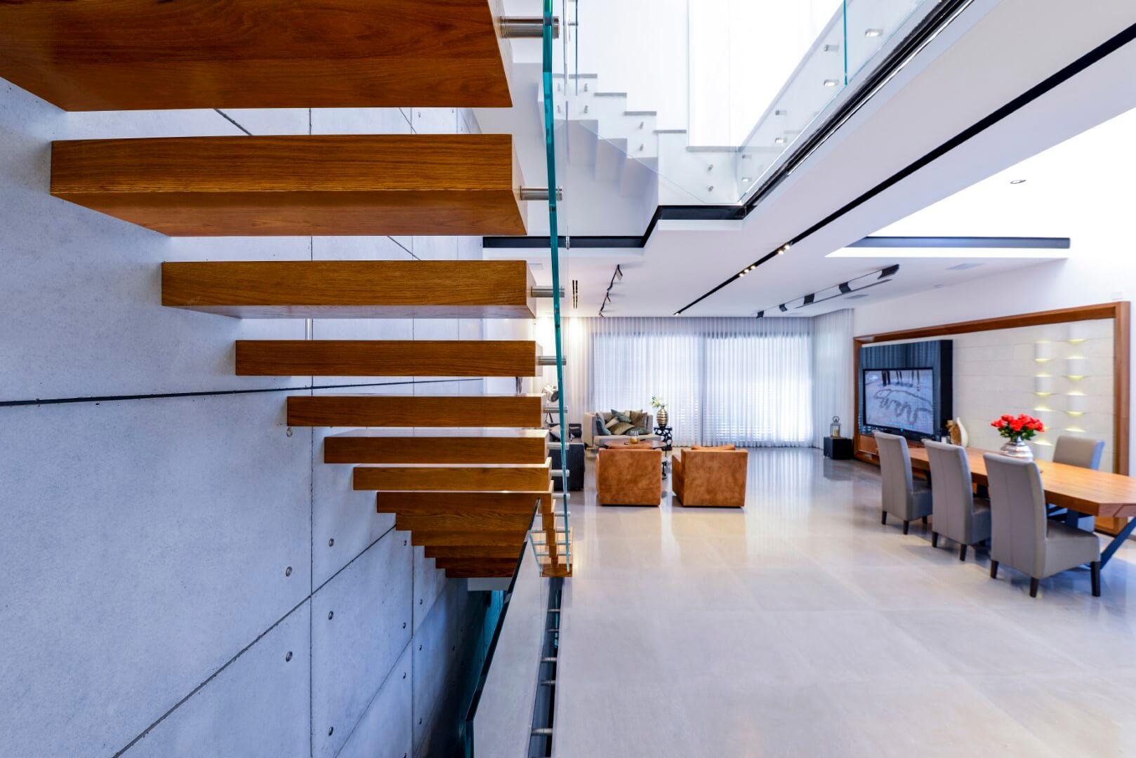 מבט אחורי על גרם מדרגות צפות מעץ אלון בגוונים של נחושות ומדבר על קיר לוחות בטון עצומים