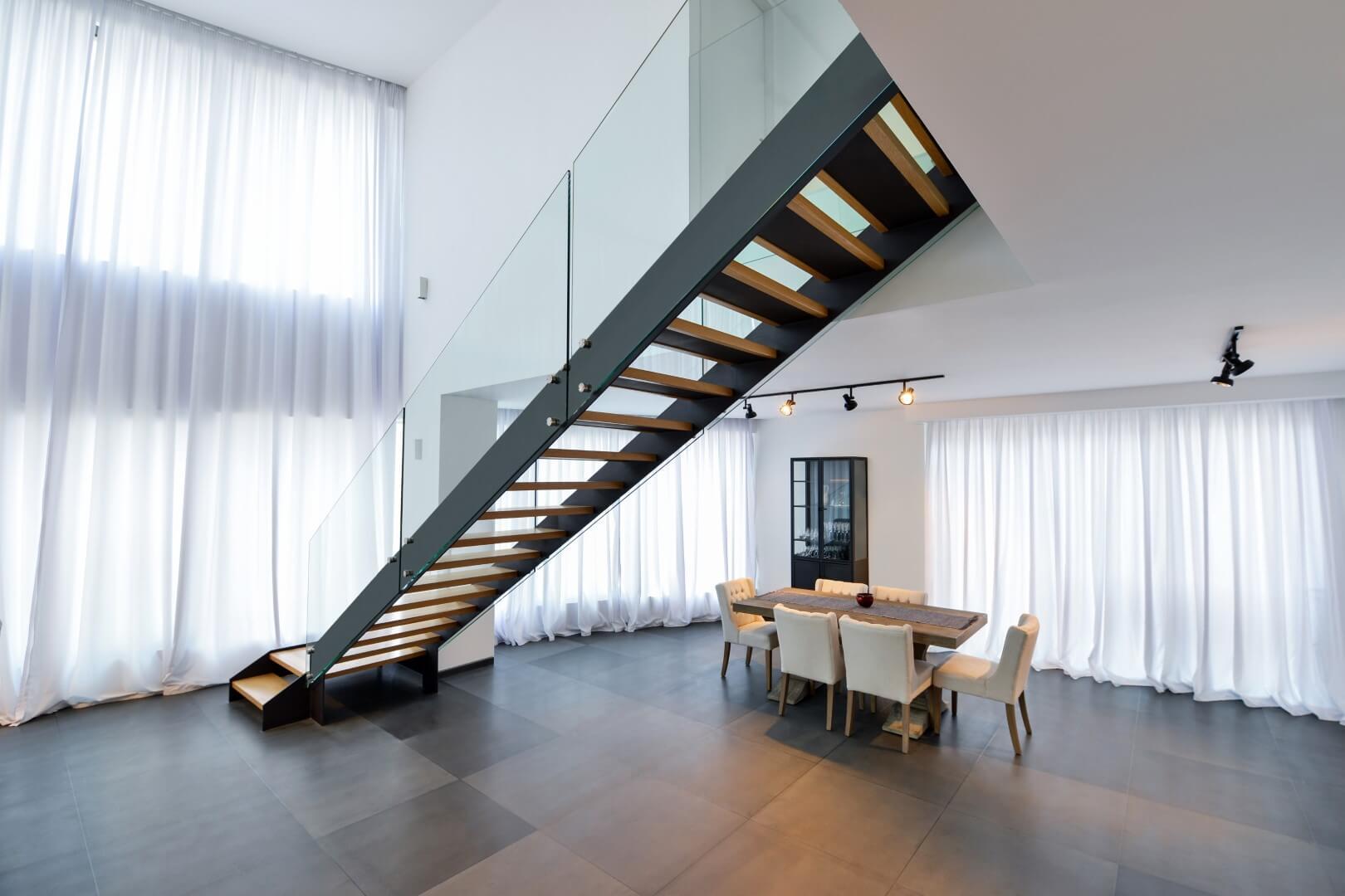 מבט אחורי על גרם מדרגות הברזל השחור שעולה מפינת האוכל אל המפלס העליון