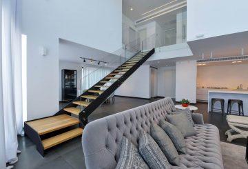 גרם מדרגות ארוך עם מדרכי עץ אלון בשילוב גוונים של חיטה וחולות נודדים על קונסטרוקצית ברזל עם מעקה זכוכית קליר