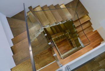 מבט דרך מעקות הזכוכית אל פיר מדרגות העץ בגוונים של ברונזה וחום שוקולד מריר