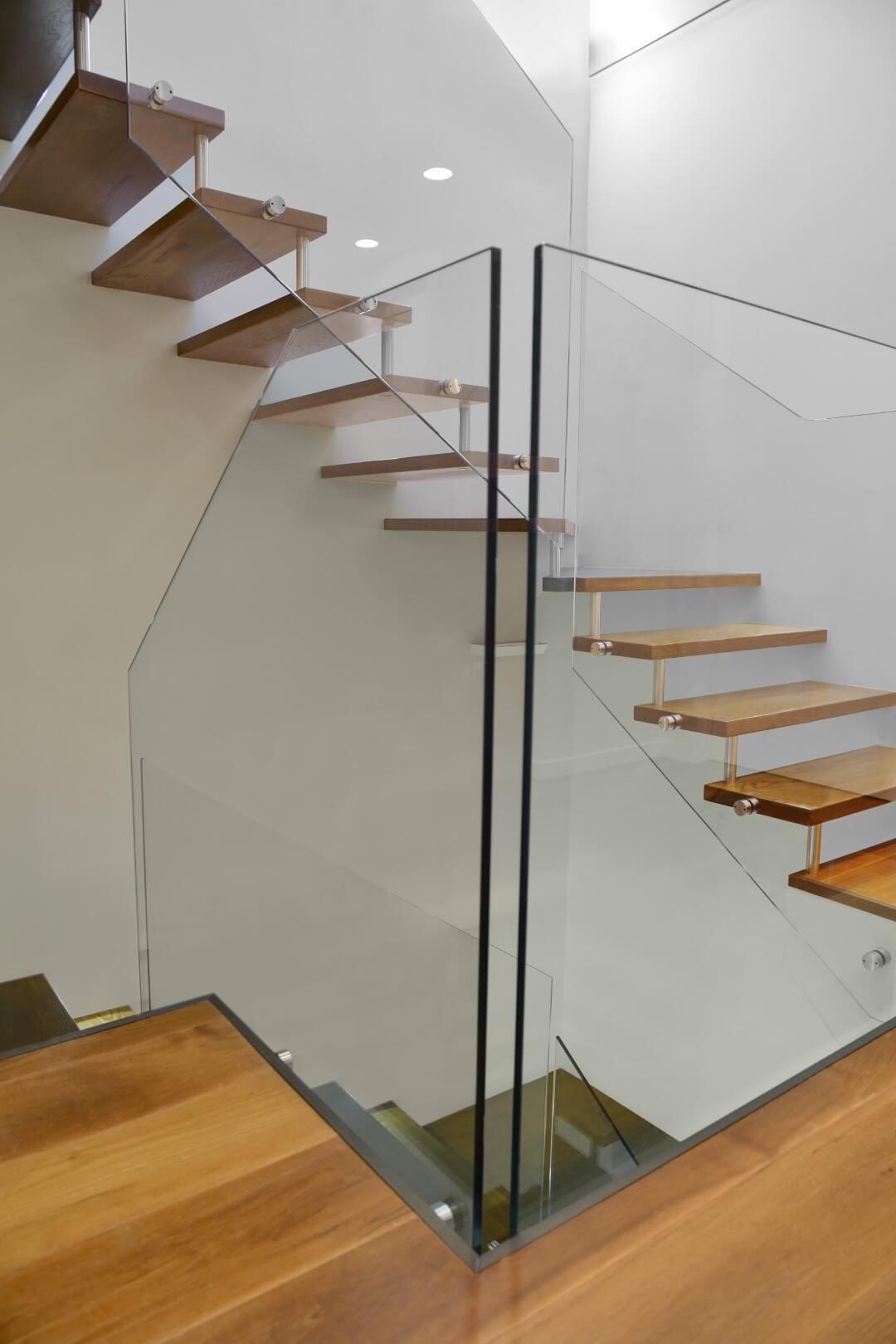 שני גרמי מדרגות עץ תלויות מבעד למעקה הזכוכית
