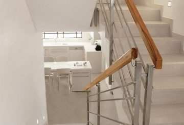 שני גרמי מדרגות באפור אבן עם מעקה נירוסטה וידית אחיזה מעץ אגוז אמריקאי בגוונים של נחושת וחום חלוד