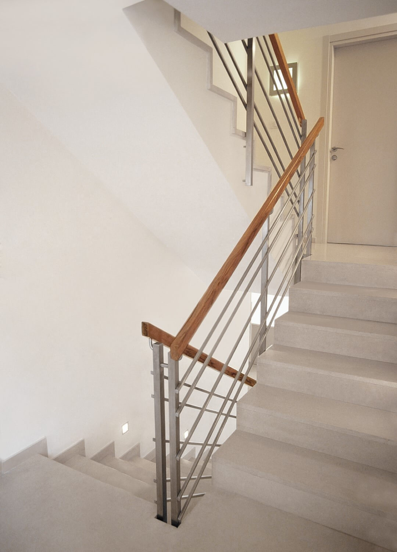 שלושה גרמי מדרגות באפור עם מעקה מוטות נירוסטה עם מאחז יד מעץ אגוז אמריקאי בגווני חום ונחושת