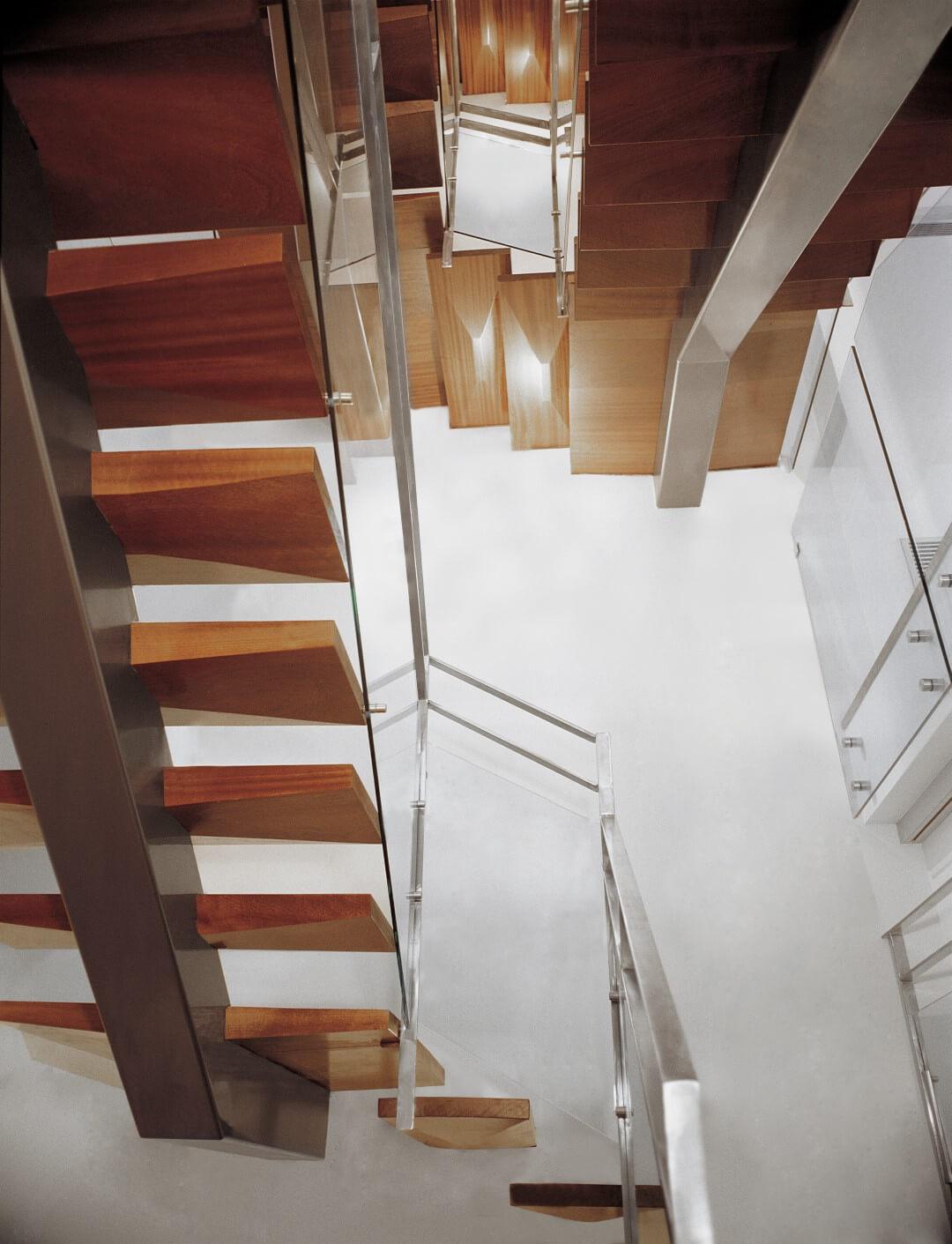 מבט על אחורי מדרגות העץ שתלויות על שדרה מרכזית של ברזל