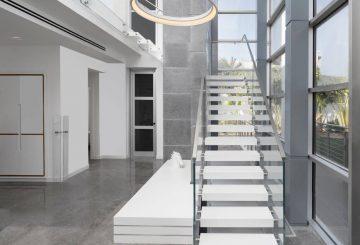 שני גרמי מדרגות צפות מקוריאן לבן עולות אל המפלס העליון בוילה