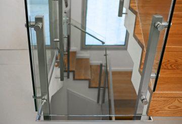 מבעד למעקה הזכוכית בשילוב נירוסטה רואים שלושה גרמי מדרגות עץ אלון