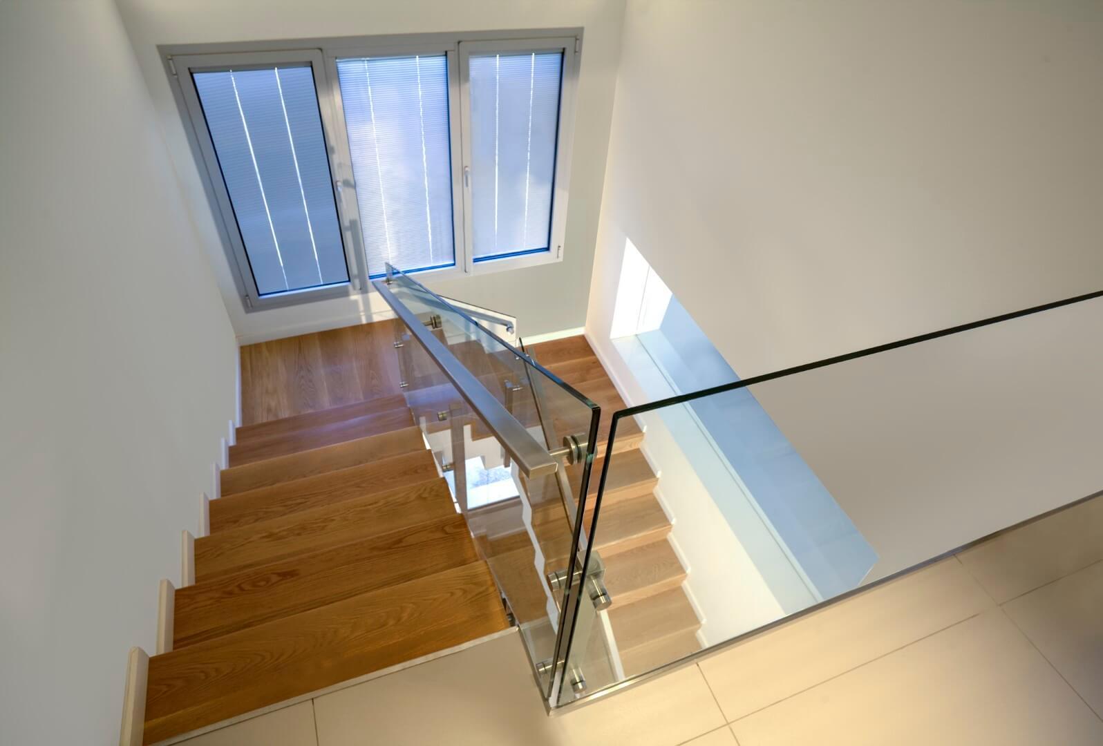 מבט מהמפלס העליון אל עבר שני גרמי מדרגות מחופות בעץ אלון אמריקאי טבעי עם מעקה זכוכית ונירוסטה