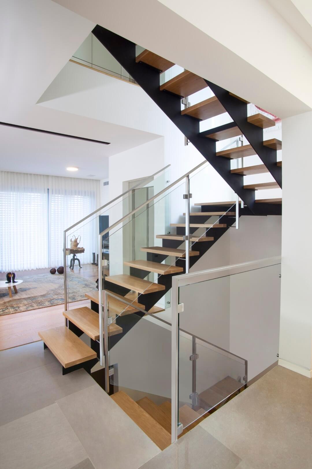 פיר המדרגות מכיל שלושה גרמי מדרגות ברזל שחור עם מדרגות עץ אלון אמריקאי ומעקה זכוכית