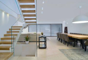 שני גרמי מדרגות ברזל לבן עם מדרכי עץ אלון בגוונים של נחושת מיושנת וחימר קדרים בליווי של מעקה זכוכית