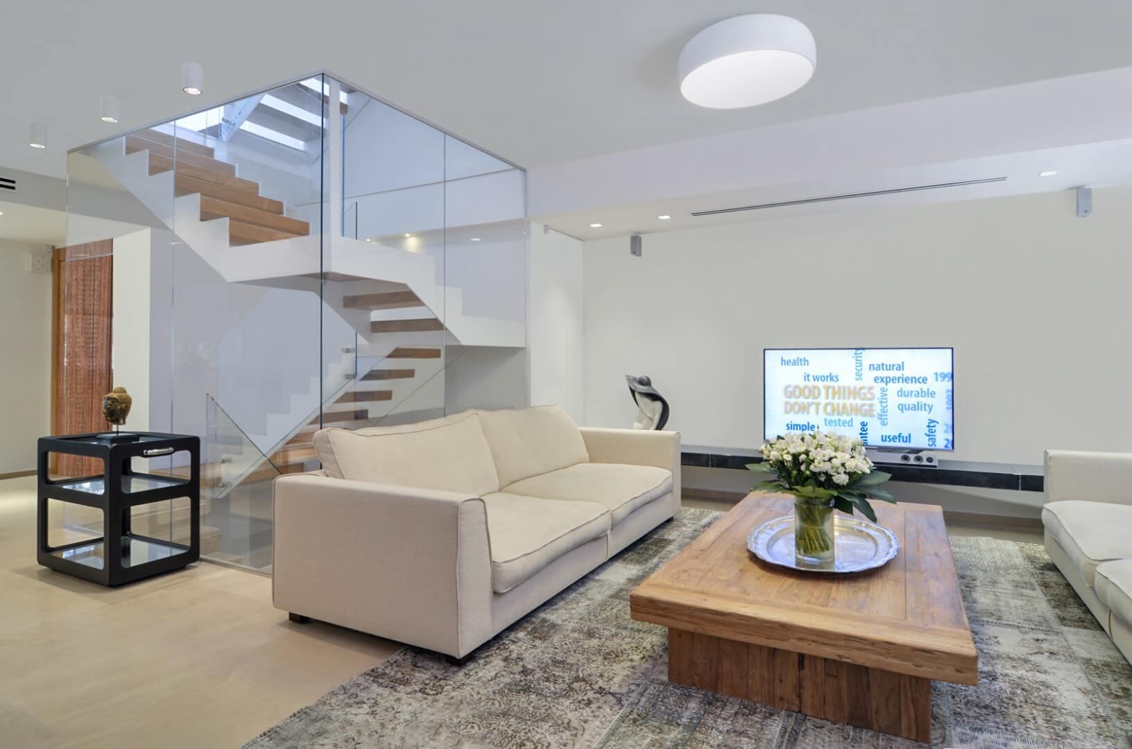 מבט מהסלון על שלושה גרמי מדרגות ברזל לבן משולב עץ אלון אמריקאי בגוון של ברונזה מטלית