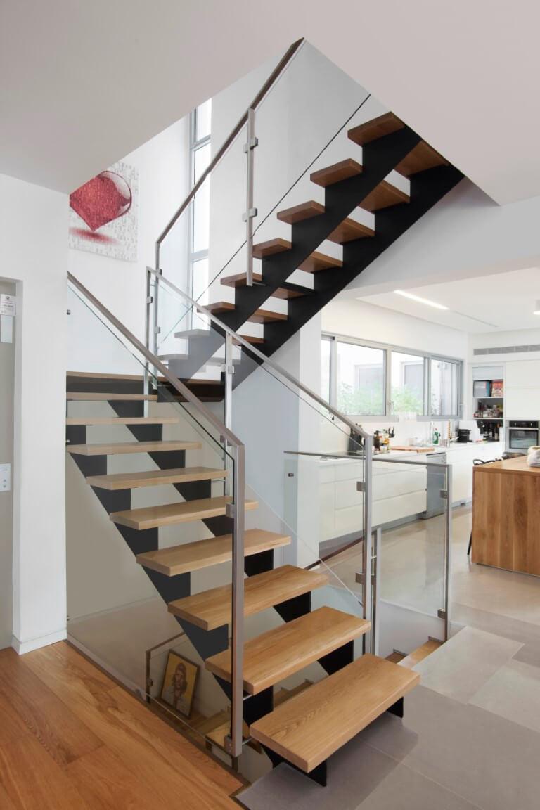שני גרמי מדרגות ברזל שחור עם מדרגות עץ אלון אמריקאי ומעקה זכוכית בסמוך למטבח